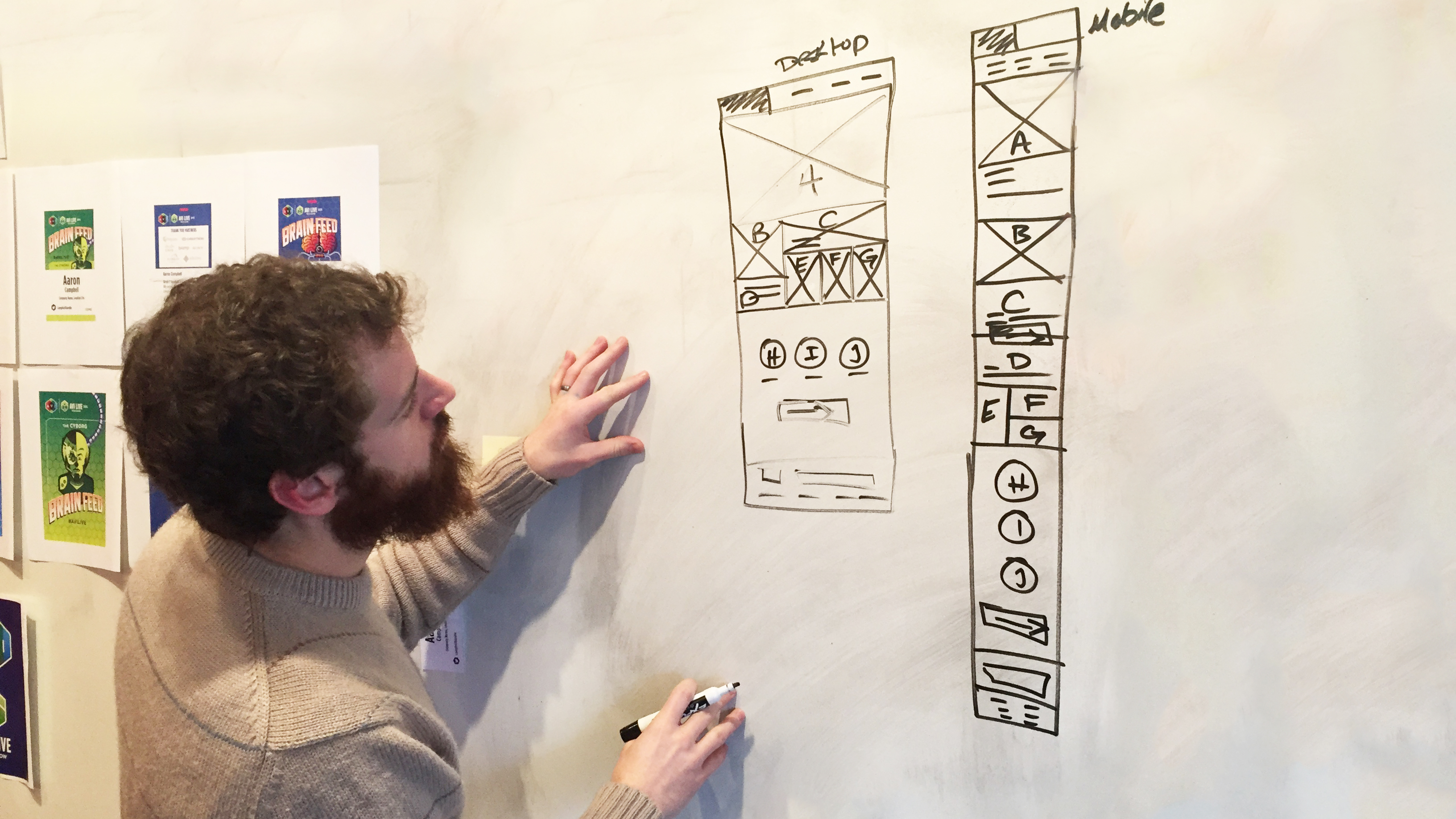 Designer sketching website wireframes on whiteboard